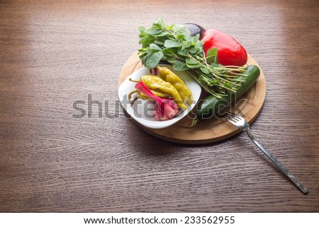 Cucumber, bell pepper, mint, marinated garlic and jalapeno on wooden board - stock photo