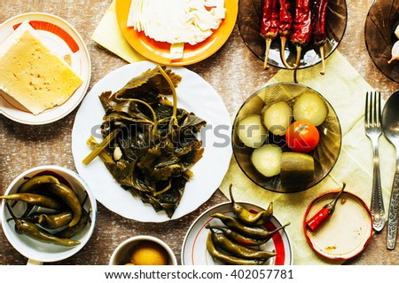 Cucumber marinated bowl with pepper and garlic.  Group of fermented veggies on the plate. Overhead view on vegetarian style dinner with vegetable soup, pickled cucumbers, pickled peppers, cabbage. - stock photo