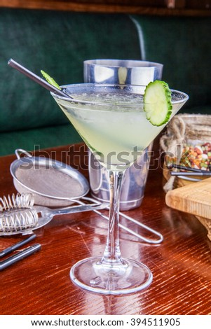 Cucumber martini cocktail on wooden table - stock photo