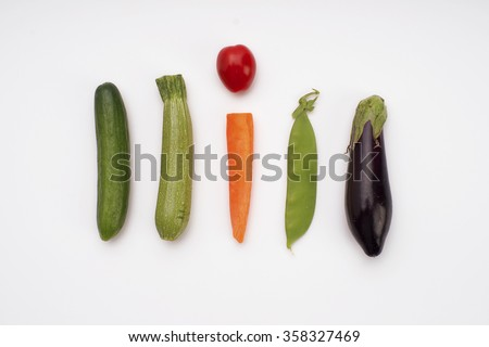 Cucumber, mini courgette ,carrot stick, cherry tomato, peas and mini eggplant. Top view of vegetables isolated on white. - stock photo