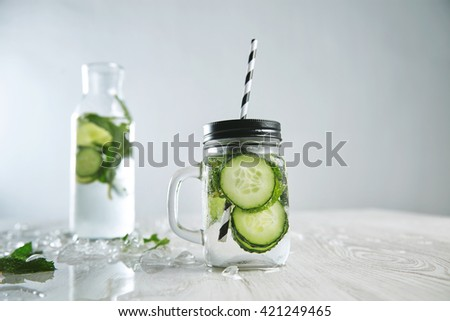 Cucumber mojito lemonade without alcohol. Fresh summer drink to cool down with mint, mineral water and ice. Rustic jar in front and bottle with beverage behind - stock photo