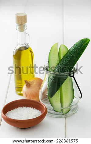 Cucumber; onion; olive oil and salt over white wooden table - stock photo