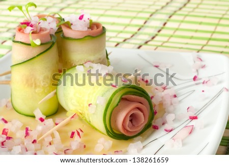 Cucumber rolls with pate and radishes - stock photo