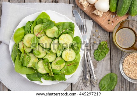 Cucumber salad with fresh leaves and sesame seeds, top view - stock photo