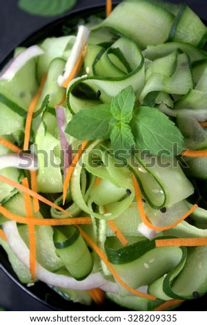 Cucumber salad with slice of carrot, nion and mint