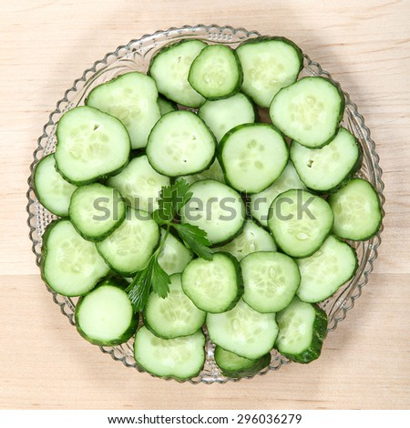 Cucumber sliced with fresh herbs on a plate isolated on white background.