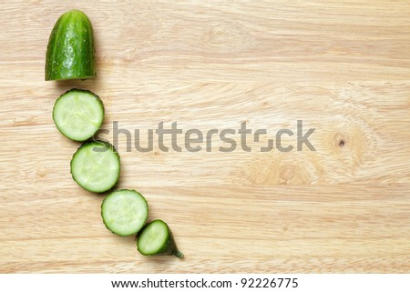 Cucumber slices on cutting board above view - stock photo