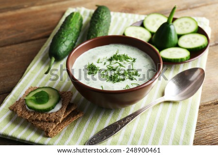 Cucumber soup in bowl on rustic wooden table background - stock photo