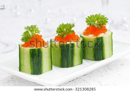 cucumber tartlets with cream cheese and red caviar, closeup, horizontal - stock photo