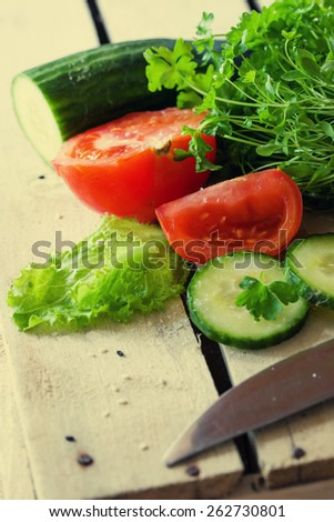 cucumber, tomato and knife on wooden background - stock photo
