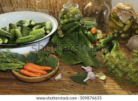Cucumbers and carrots prepared for canning on a wooden table - stock photo