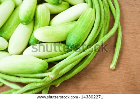 Cucumbers and green beans on plywood