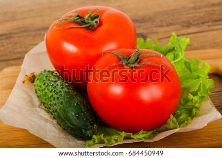 Cucumbers and tomatoes with salad leaves over wooden background