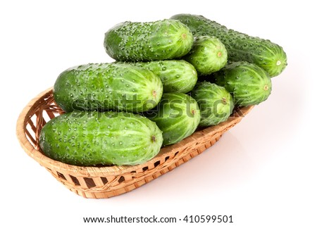 cucumbers in a wicker basket isolated on white background