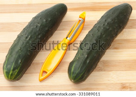 Cucumbers ready for peeling with peeling tool. - stock photo