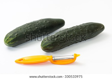 Cucumbers ready for peeling with peeling tool on white background. - stock photo