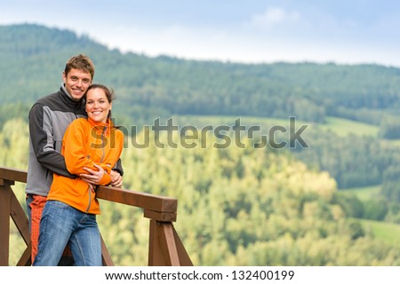 Cuddling couple on a summer weekend at the top of the mountain - stock photo