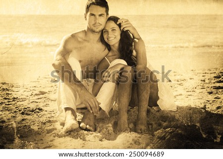 Cuddling couple smiling at camera against grey background - stock photo