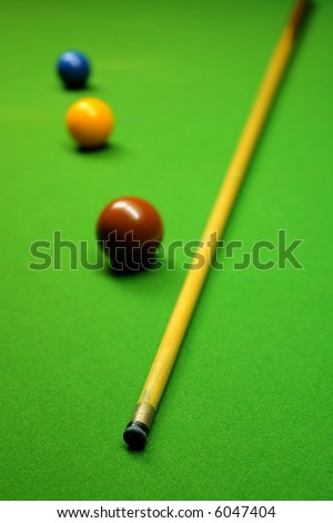 Cue stick and snooker balls over green surface, shallow depth of field - stock photo