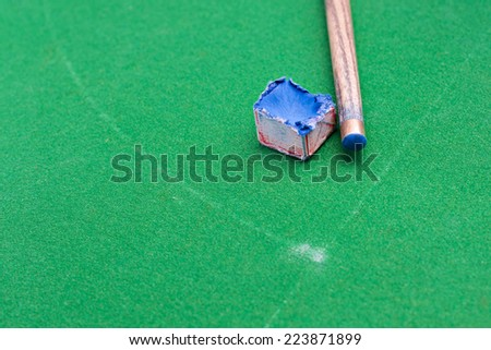 Cue stick with chalk block. - stock photo