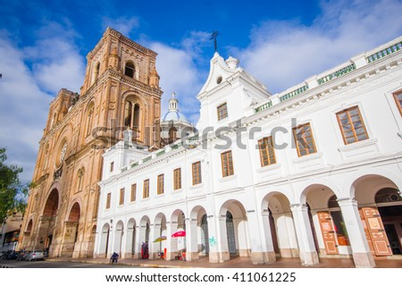 Cuenca, Ecuador - April 22, 2015: Spectacular main cathedral located in the heart of city, beautiful brick architecture and facade as seen from street level - stock photo