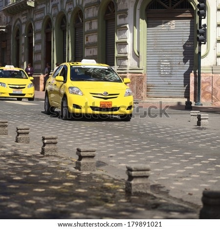 CUENCA, ECUADOR - FEBRUARY 13, 2014: Taxi on the Mariscal Sucre Avenue on February 13, 2014 in the city center of Cuenca, Ecuador - stock photo
