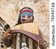 CUENCA, ECUADOR - MAY 27: Andean Indian plays traditional instrument on May 27, 2011 in Cuenca, Ecuador. Indigenous descendants are found in the towns of the Andes mountain range in South America. - stock photo