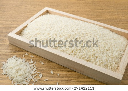 Cuisine and Food, Uncooked White Long Rice, Basmati Rice or Jasmine Rice in A Wooden Tray. - stock photo