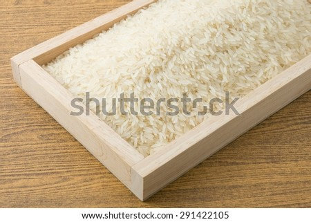 Cuisine and Food, Uncooked White Long Rice, Basmati Rice or Thai Jasmine Rice in Wooden Tray. - stock photo