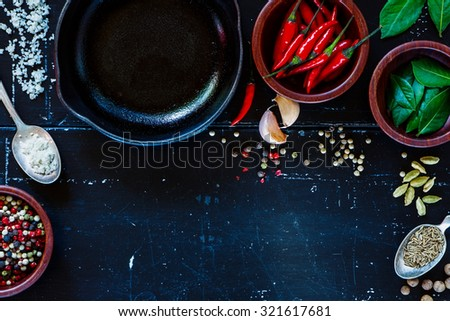 Cuisine ingredients on dark vintage texture. Spices and herbs selection. Top view. Background with space for text. - stock photo