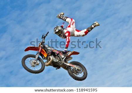 CULHAM, UK - SEPTEMBER 22: An unnamed stunt rider from the X-fighter team pulls a one handed air stunt for the watching public at the Red Bull Pro Nationals MX series on September 22, 2012 in Culham - stock photo