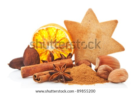 Culinary aromatic spices christmas background. Anise, cinnamon and various nuts. Star shaped gingerbread cookie and orange slice in background on white. Traditional xmas still life.