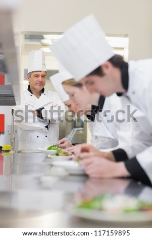 Culinary class making salads as teacher is supervising in kitchen - stock photo