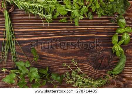 Culinary herbs background with copy space. Fresh basil, cilantro, chive, parsley and mint herbs on brown wooden background with copy space. - stock photo