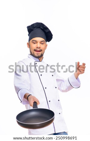 Culinary magic. Skillful concentrated handsome cook working with a frying pan while standing against grey background with copy space - stock photo