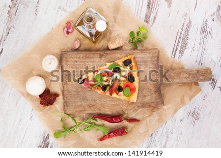 Culinary pizza cooking. Pizza piece on wooden kitchen board, with various ingredients and toppings. Fresh herbs, olive oil, garlic, edible mushrooms, dried tomatoes and chili pepper. Pizza eating. - stock photo