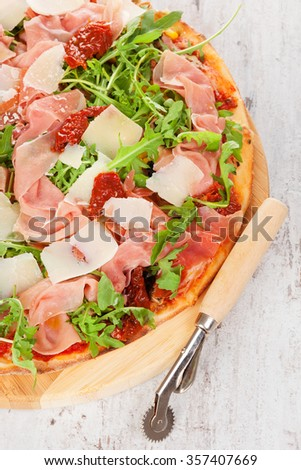 Culinary pizza with prosciutto, dry tomatoes and fresh herbs on wooden cutting board on wooden table.