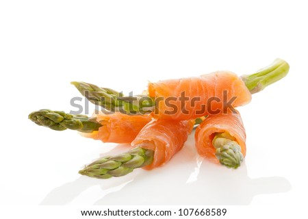 Culinary seafood background. Asparagus wrapped in raw salmon. - stock photo