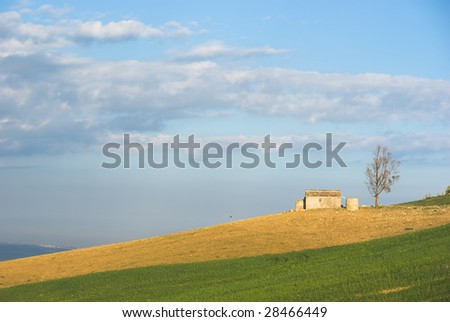 cultivated land with farm and tree - stock photo