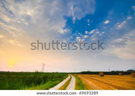 Cultivated meadows in the sunset - Italy - stock photo