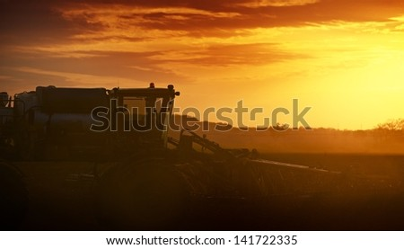 Cultivating in Sunset. Tractor Works on the Field. Agriculture Works Photography Collection. - stock photo