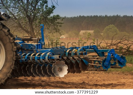 cultivator stands on ground road by ploughed field against village and forest - stock photo