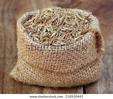 Cumin in sack bag on wooden surface - stock photo
