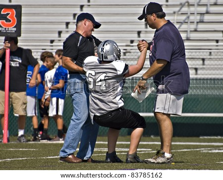 CUMMING, GA - AUGUST 27: Unidentified injured player helped off the field during a game of 11-13 year-old boys, August 27, 2011 in Cumming GA. The Raiders vs The War Eagles. - stock photo