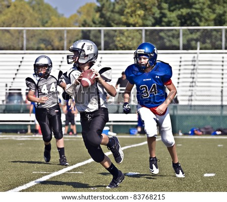 CUMMING, GA,USA - AUGUST 27:  A group of 11 to 13-year-old unidentified boys during a football game, one is ready to throw a pass, the Raiders vs the War Eagles, on August 27, 2011 in Cumming GA. - stock photo