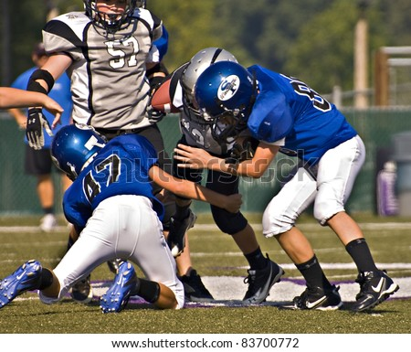 CUMMING, GA, USA - AUGUST 27: A team of 11 to 13-year-old unidentified boys during a tackle at a football game, the Raiders vs the War Eagles, on August 27, 2011 in Cumming GA. - stock photo