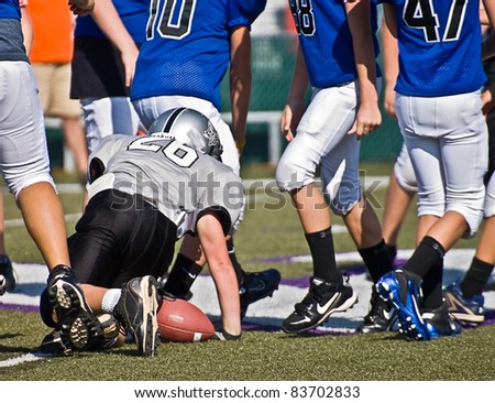 CUMMING, GA, USA - AUGUST 27: Andy Leggett, on the ground, after being tackled during a football game comprised of 11-13 year old boys on August 27, 2011 in Cumming GA. It is the Raiders vs the  War Eagles game. - stock photo