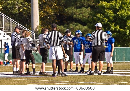 CUMMING, GA, USA - AUGUST 27: Unidentified 11 to 13 year-old boys getting pre-game instructions at a football game, The Raiders vs The War Eagles on August 27, 2011 in Cumming GA. - stock photo