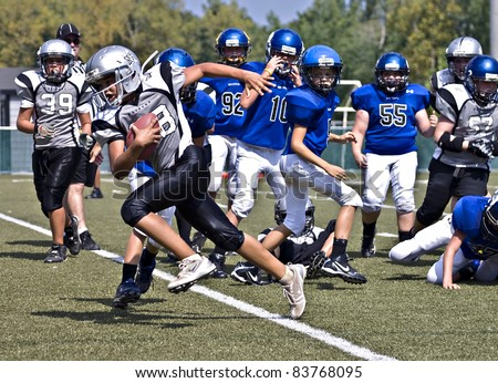 CUMMING, GA,USA - AUGUST 27: Unidentified 11 to 13 year-old boys watching as Reed Davis runs for a touchdown. August 27, 2011 in Cumming GA. The Raiders vs The  War Eagles. - stock photo