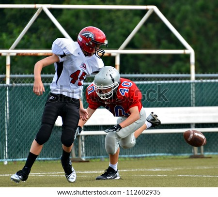 CUMMING, GA/USA - SEPTEMBER 8: Andy Leggett making a tackle on an unidentified opponent during a football game of 7th grade boys September 8, 2012 in Cumming GA. The Wildcats  vs The Mustangs. - stock photo